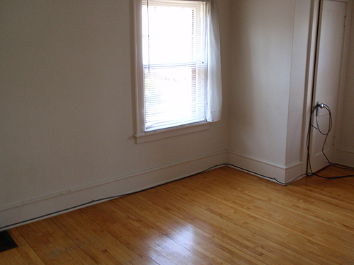 The third bedroom at 115 Bulkley with hardwood floors, a double hung window, and a floor vent.