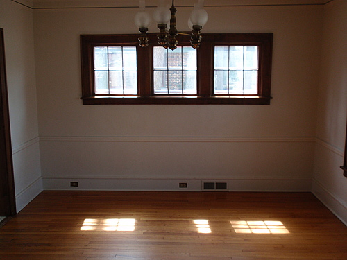 The dining room at 115 Bulkley. It has hardwood flooring, hang lighting, and three small windows.