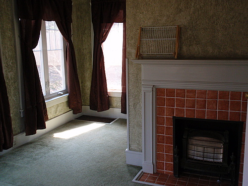 The second view of the carpeted downstairs sunroom with a fireplace, large floor vent, and more casement windows.