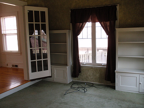 The downstairs, carpeted sunroom with two built in shelves flanking a large casement window. The sunroom is also a step down from another room.