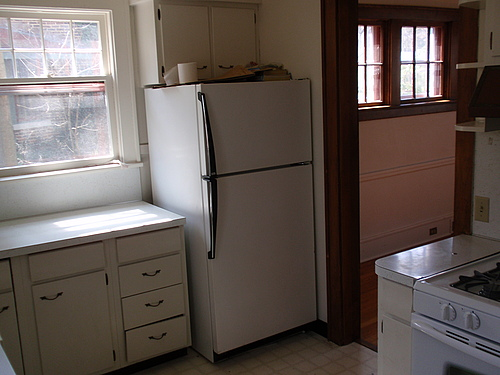 The kitchen at 115 Bulkley, with an oven, stove, refrigerator, and double hung window.