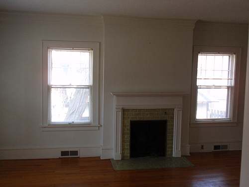 The living room at 115 Bulkley with hardwood floors, flush baseboard vents, and two double dung windows flanking the fireplace.